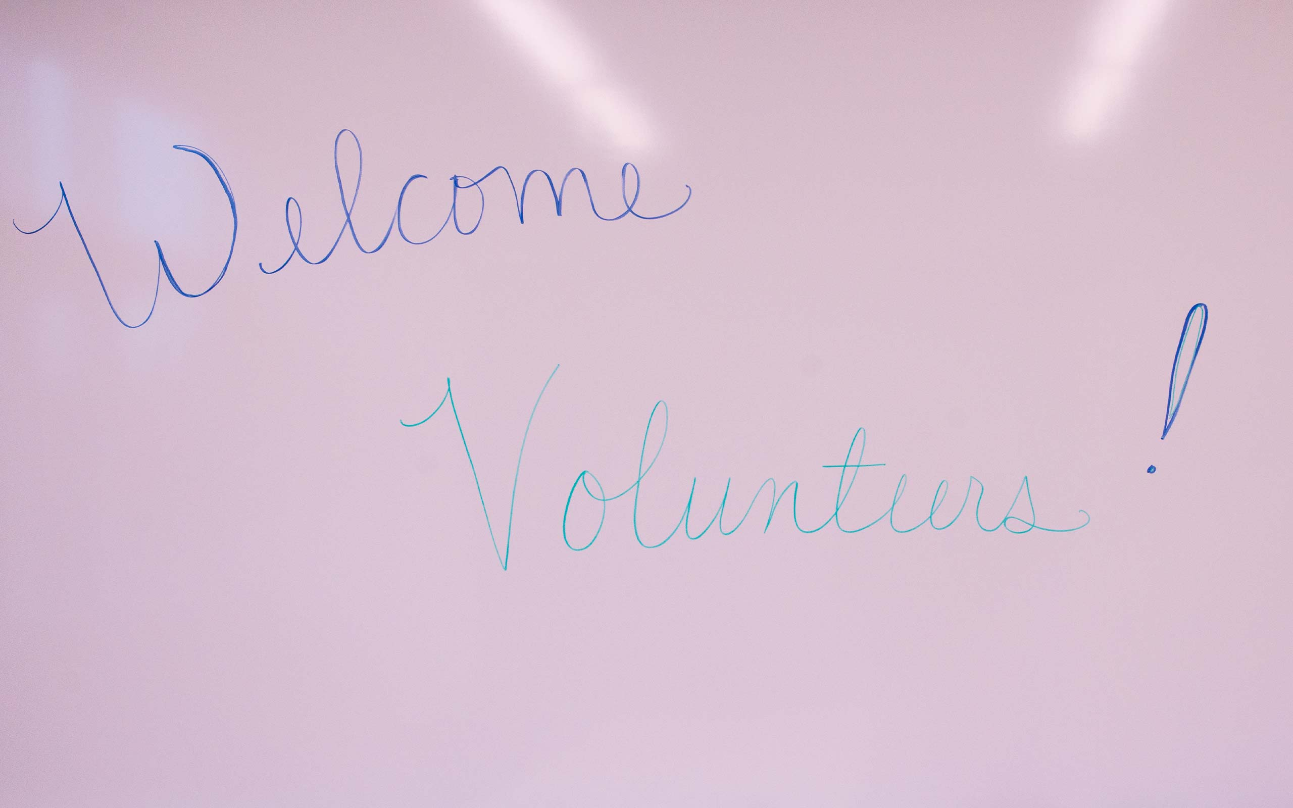 "A whiteboard that says ""Welcome, Volunteers"""