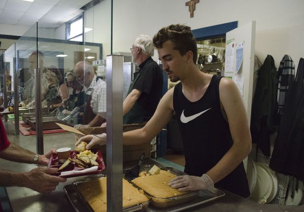 A volunteer serves food at the St. Francis Dining Hall
