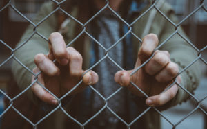 Hands gripped around a chain-link fence.